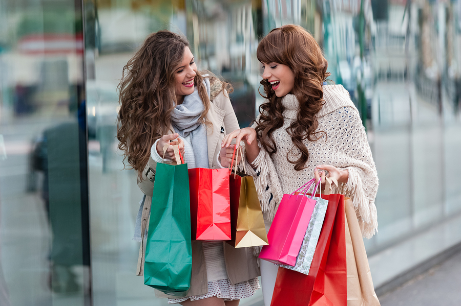 Two attractive young women shopping together,holding shopping bags and gift boxes,with red christmas hat,smiling while standing in front of shop window. Outdoors.